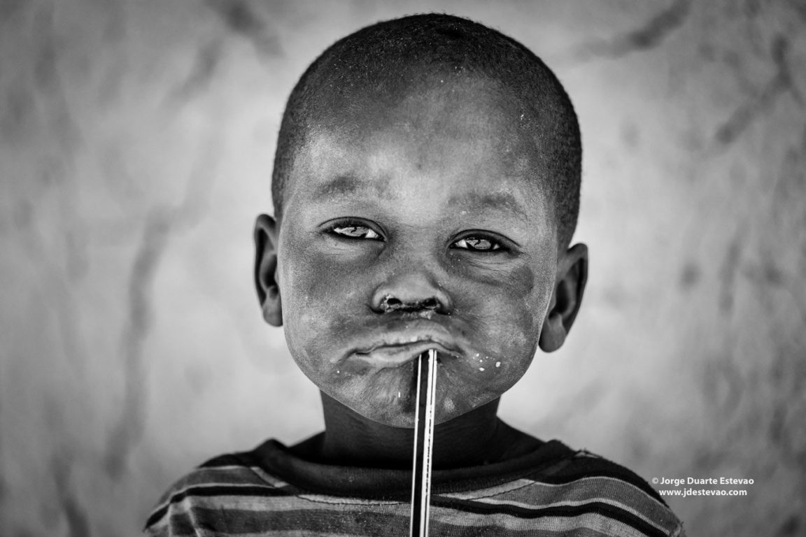 Himba are indigenous people living in Namibia. A Himba child takes a short break from school to meet foreign travellers