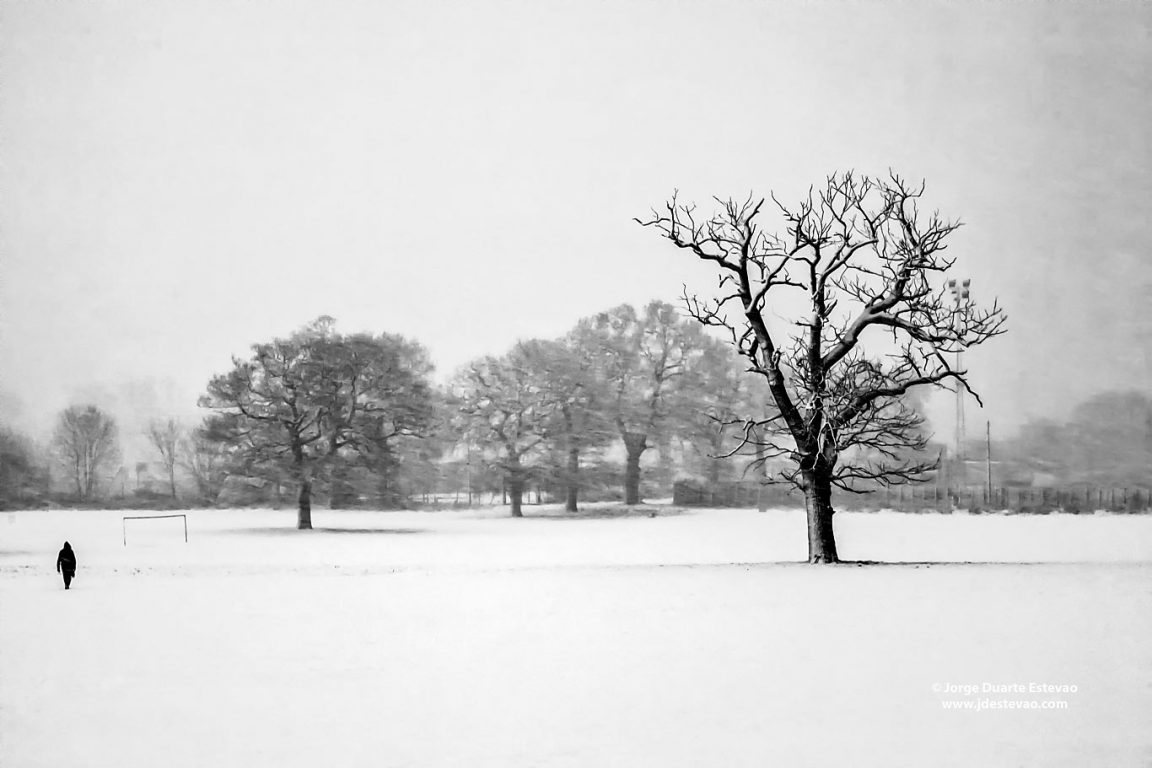 A person crosses a snow covered football pitch in Raynes Park, southwest London, England