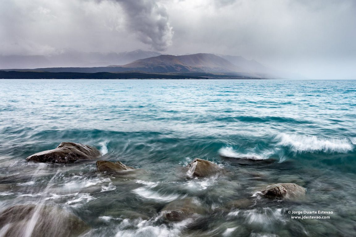 The drama on the shores of the turquoise waters of Lake Tekapo, New Zealand. The lake gets its vivid colour from the rock-flour carried down the valley from the glaciers