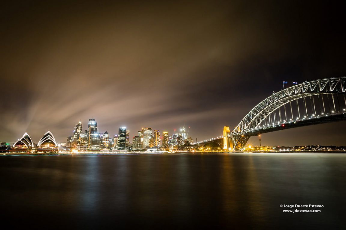 Night setting over Sydney Harbour bridge and Sydney Opera House. The latter is an iconic multi-venue performing arts centre in Sydney, Australia
